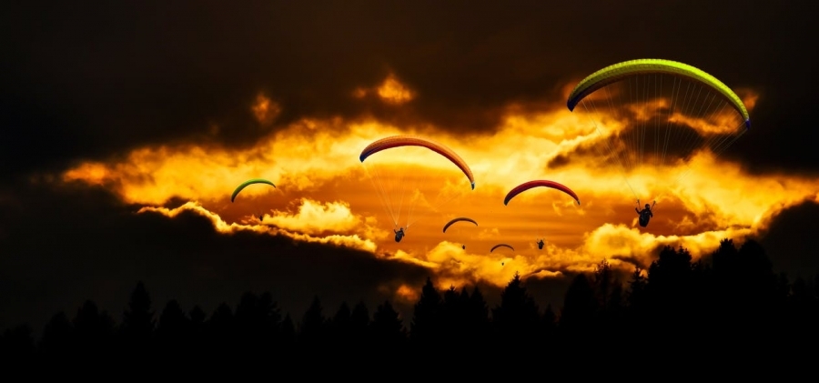 people-in-mid-air-using-parachute-in-dusk
