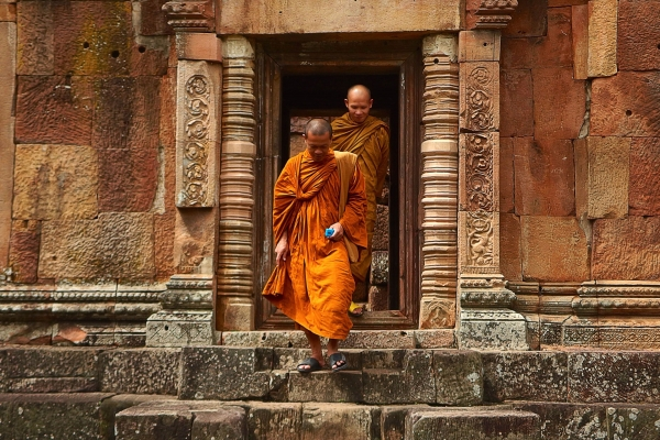 two-monk-in-orange-robe-walking-down-the-concrete-stairs
